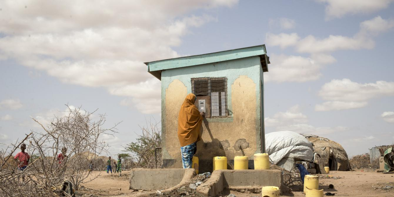 A woman uses her water credit, which is stored in a small, plastic token, to buy water from a Water ATM in Hadado, Kenya.  Credit Katie G. Nelson/Oxfam