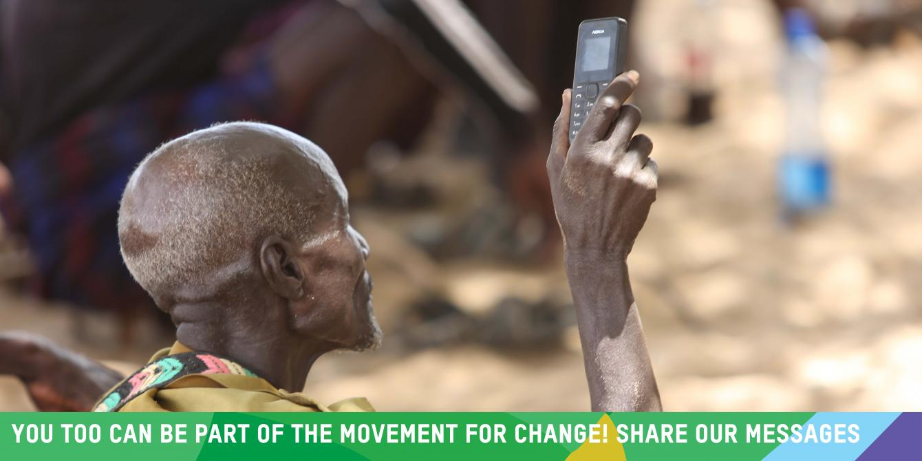 Turkana man holds out his mobile phone during a public baraza on oil and community rights in Lokichar, Turkana. Photo Credit: LightBox Limited